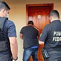 Agentes da Receita e da PF esperam abertura de quarto de hotel durante operação.